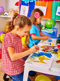 Маленькая девочка группы с картиной щетки в детском саде Стоковая Фотография