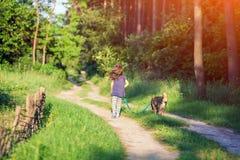 Маленькая девочка гуляя с собакой Стоковые Фотографии RF