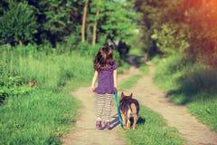 Маленькая девочка гуляя с собакой Стоковые Изображения