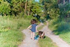 Маленькая девочка гуляя с собакой Стоковые Изображения RF