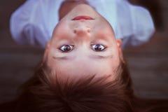 Маленькая девочка лежа и смотря вас стоковая фотография rf
