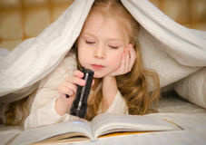 Маленькая девочка лежа на кровати и читая книгу Стоковые Изображения