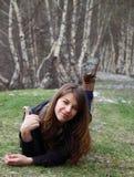 Маленькая девочка лежа на траве и выставки О'КЕЫ вручают знак Стоковая Фотография RF