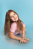 Маленькая девочка лежит на голубой предпосылке Стоковое Изображение