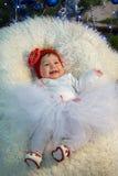 Маленькая девочка лежит на одеяле и смеется над Стоковое фото RF