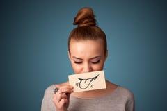 Маленькая девочка держа белую карточку с чертежом улыбки на предпосылке градиента Стоковые Изображения RF