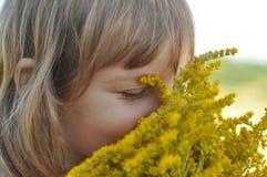 Маленькая девочка держа букет цветков лета поля и пахнуть ей с ей глаза закрыла Стоковое Изображение