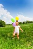 Маленькая девочка держа 3 воздушного шара летая в парке Стоковая Фотография RF