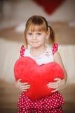 Маленькая девочка держа в форме сердц подушку красный цвет поднял мати Стоковое Фото