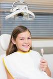 Маленькая девочка держа зубную щетку в стуле дантистов Стоковое Изображение RF