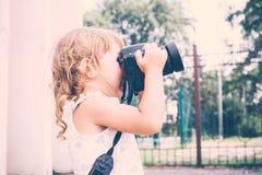 Маленькая девочка держа камеру и фотографируя Стоковые Изображения