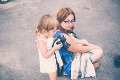 Маленькая девочка держа камеру и фотографируя Стоковое Фото