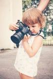 Маленькая девочка держа камеру и фотографируя Стоковое фото RF
