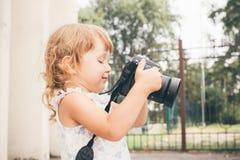 Маленькая девочка держа камеру и фотографируя Стоковые Фото