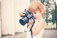 Маленькая девочка держа камеру и фотографируя Стоковая Фотография