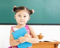 маленькая девочка держа книгу в классе Стоковые Изображения RF