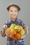 Маленькая девочка держа корзину яблок и апельсинов стоковое изображение rf