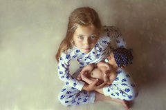 Маленькая девочка держа младенца стоковая фотография rf