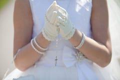 Маленькая девочка держа розарий вокруг ее gloved рук которые сжиманы в молитве Стоковое Изображение