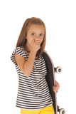 Маленькая девочка держа розовую руку скейтборда над ртом стоковые фотографии rf