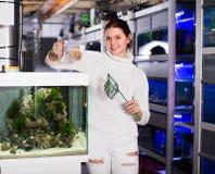 Маленькая девочка держит сеть рыб aquarian и контейнер воды Стоковые Изображения