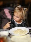 Маленькая девочка есть лапши в кафе Стоковая Фотография