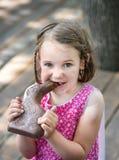 Маленькая девочка есть зайчика шоколада Стоковое Изображение RF