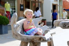 Маленькая девочка есть конус мороженого в городе стоковое изображение