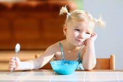 Маленькая девочка есть овсяную кашу для завтрака стоковые изображения