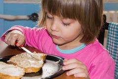 Маленькая девочка есть ломоть хлеба с pate Стоковое фото RF