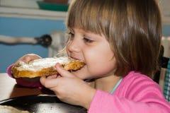 Маленькая девочка есть ломоть хлеба с pate Стоковые Изображения