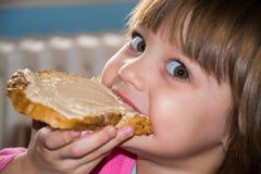 Маленькая девочка есть ломоть хлеба с pate Стоковые Фото