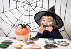 Маленькая девочка есть печенья на хеллоуине, фокусе детей или обрабатывать стоковое фото rf