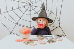 Маленькая девочка есть печенья на хеллоуине, фокусе детей или обрабатывать стоковая фотография