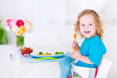 Маленькая девочка есть салат для обеда Стоковые Фотографии RF