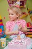 Маленькая девочка есть торт на вечеринке по случаю дня рождения Стоковые Изображения