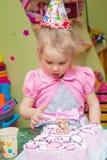 Маленькая девочка есть торт на вечеринке по случаю дня рождения Стоковое фото RF