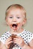 Маленькая девочка есть шоколад Стоковое Изображение