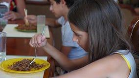 Маленькая девочка ест лапши гречихи с вилкой скрепя сердце Ребенок отказывает съесть Стрельба замедления видеоматериал