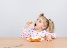 Маленькая девочка ест морковь с вилкой Стоковые Изображения RF