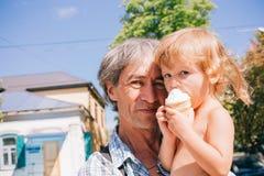 Маленькая девочка ест мороженое сидя на ее отце ` s Стоковые Фото