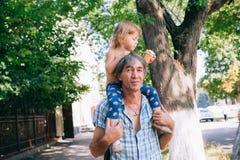 Маленькая девочка ест мороженое сидя на ее отце ` s Стоковые Фотографии RF