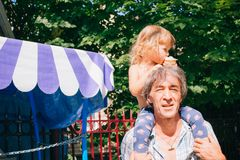 Маленькая девочка ест мороженое сидя на ее отце ` s Стоковое фото RF