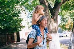 Маленькая девочка ест мороженое сидя на ее отце ` s Стоковая Фотография