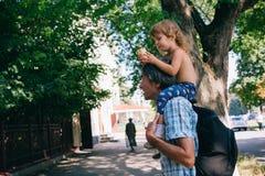 Маленькая девочка ест мороженое сидя на ее отце ` s Стоковое Изображение