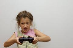 Маленькая девочка детей держа видеоигру игры кнюппеля счастливую Стоковое Изображение