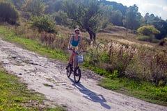 Маленькая девочка ехать велосипед на дороге Стоковое фото RF