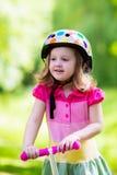 Маленькая девочка ехать красочный самокат Стоковая Фотография RF