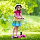 Маленькая девочка ехать красочный самокат Стоковая Фотография