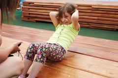 Маленькая девочка делает подбрюшные хрусты стоковая фотография